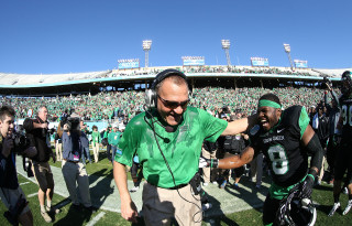 DENTON, TX JANUARY 1: Head coach Dan McCarney of the North Texas Mean Green puts his arm on Mark Lewis #8 of the North Texas Mean Green after the Heart of Dallas Bowl at Cotton Bowl Stadium in Dallas on January 1, 2014 in Dallas, TX. Photo by Rick Yeatts