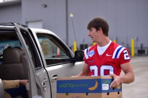 Bulldog sophomore punter Gerald Shouse greets passengers before loading food in a vehicle. (Action Sports and News/Greg Collier)