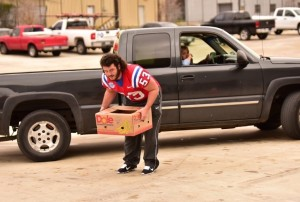 Bulldog sophomore longsnapper Darrell Travis helps load a box of food onto a truck. (Action Sports and News/Greg Collier)