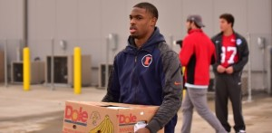 A member of the Illinois Football Team delivers a  package to a family in need. (Action Sports and News/Greg Collier)